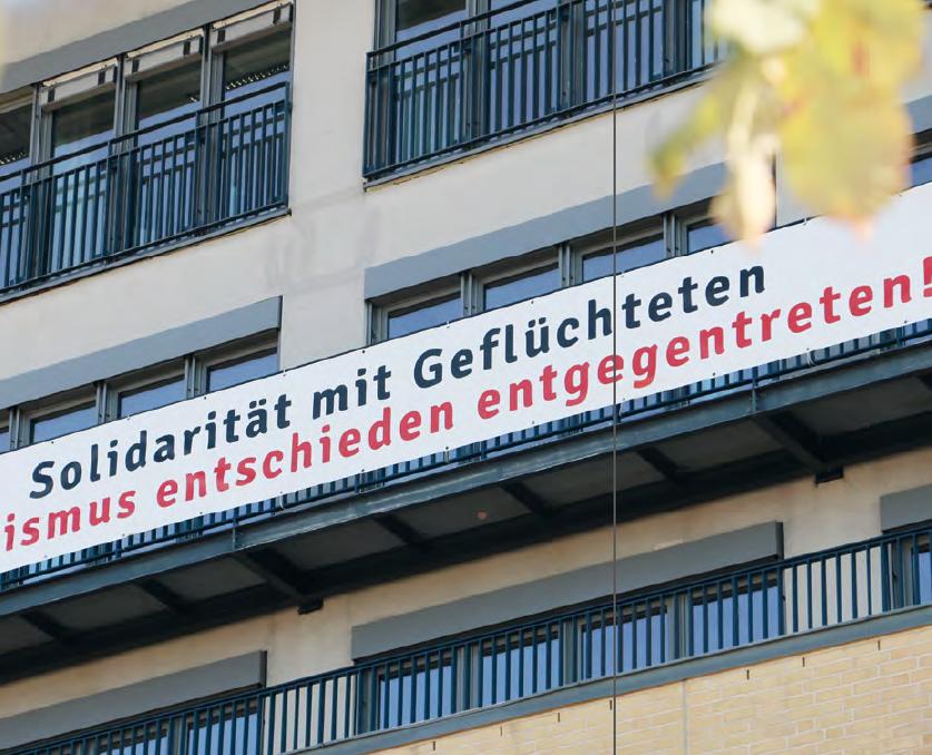 """Ein Banner an der Fassade der Alice Salomon Hochschule mit der Aufschrift: """"Solidarität mit Geflüchteten. Rassismus entschieden entgegentreten!"""""""