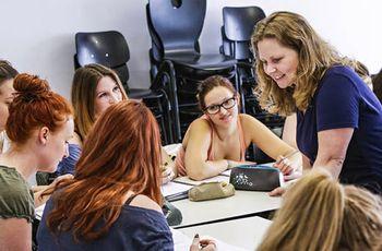 Unterrichtssituation: Eine Sprachlehrerin arbeitet mit einer Gruppe Studierender an einem Tisch.
